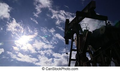 Oil rig pumping over sky Loop footage