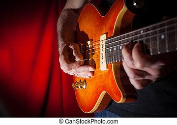Playing guitar - Man playing electric guitar at red...