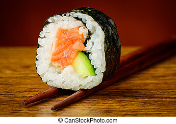 Futomaki sushis roll on chopsticks - Futomaki sushi roll on...