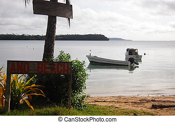 Boat near beach with timber name plate