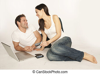 buyers couple - Couple shopping on internet paying by credit...