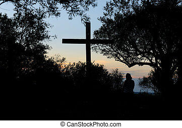 Person in front of cross - Person kneeling in front of cross...