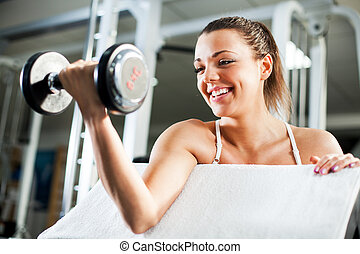 Young woman doing Biceps exercise - Cute Sporty young woman...