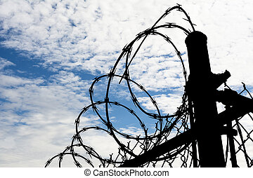 Prison Fence Against Dark Sky - A barbed wire prison fence...