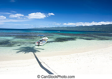 Classic tropical beach - A boat floats along the shore of a...