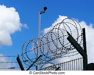 Restricted area - fence with barbed wire and camera