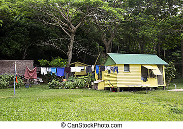 Shack with hanging laundry - A remote yellow shack near the...