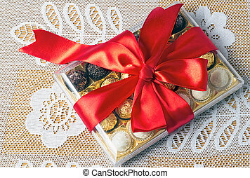 A beautifully decorated and tied with a ribbon box of chocolates, gift by a holiday, celebration, anniversary.