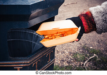 Throwing away chips - Closeup on a hand putting a box of...