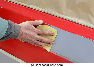 Car painting - Car ready for repaint, worker sanding primer