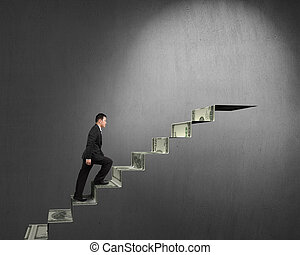 Businessman climbing on money stairs to top with spot light