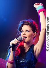 Pop star with hand raised - Young beautiful pop star with...