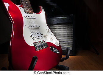 red and white electric guitar and combo amplifier on black...