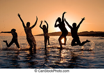 Silhouette of family jumping on the beach on beautiful...