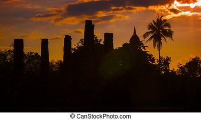 Silhouettes of the ruins of ancient temples at sunset. Thailand, Sukhothai