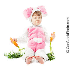 baby in easter bunny costume holding fresh carrot, kid girl in hare suit sitting over white background