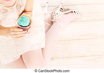 Woman holding a cupcake - A picture of a woman holding a...