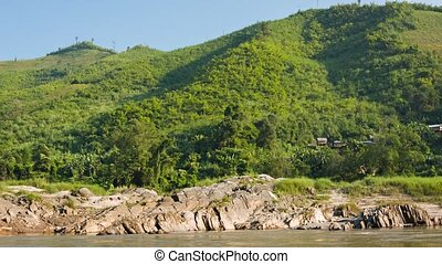 Rocky shore of the Mekong river. View from the boat. Laos -...