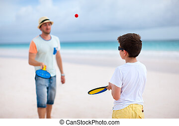 Father and son playing beach tennis on summer vacation