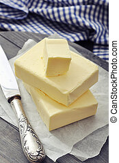 Fresh butter on wooden cutting board with knife closeup