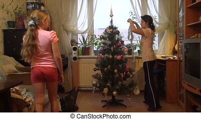 Mother with daughter decorate the Christmas tree