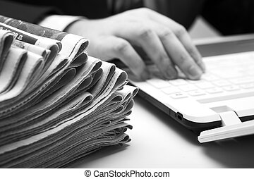 stack of newspapers in office close-up on white