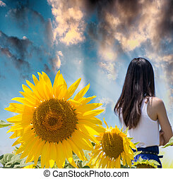 Woman in the middle of a sunflowers field at sunset.