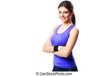 Young smiling sport woman standing with arms folded isolated...
