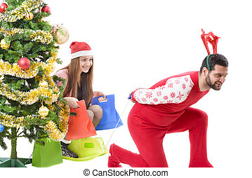 Christmas Wish - Young couple playing as santa and reindeer,...