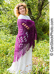 Woman in a knitted shawl in nature