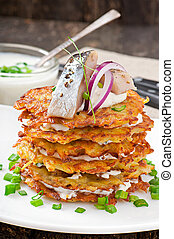 Fried potato pancakes with herring on the old wooden...