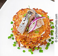 Fried potato pancakes with herring