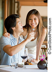 Couple Having Dinner - A young Asian couple having dinner at...