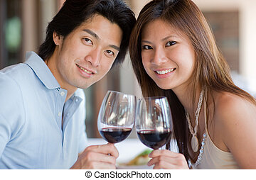 Couple At Dinner - A young couple with red wine at a...