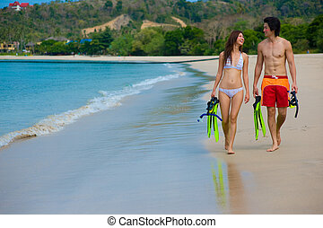 Couple On Beach - A young couple with snorkelling gear on a...