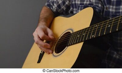 Man playing acoustic guitar, unplugged performance.