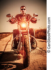 Biker on a motorcycle - Biker man wearing a leather jacket...