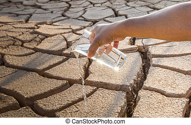 Parched Soil and Water - Male hand holding a glass of water...