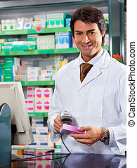 pharmacist - portrait of mid adult pharmacist scanning...