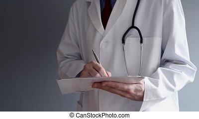 Male doctor is writing prescription while standing. Health...