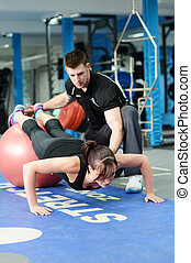 Press ups on gym ball - Personal trainer helping young woman...