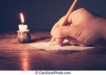 Writing by candlelight - Closeup on a hand writing by...