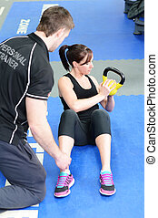 Working out with kettle bell - Young woman working out with...