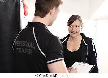 Personal Trainer writing training notes - Male personal...