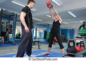 Young woman exercising with kettle bell weight - Young woman...