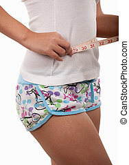Measuring the waistline - Womans body wearing shorts using a...