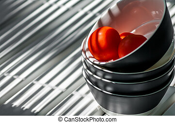 plates stacked on the table in the band with three tomatoes