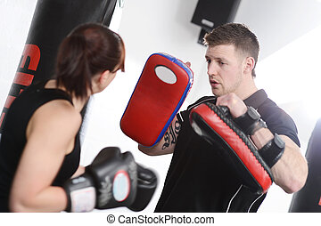 Woman punching pads with trainer - Working out with mitts or...