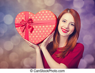 Redhead girl with shape heart box Photo red background with...