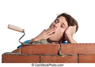 Bored bricklayer yawning - A bricklayer bored with his work...